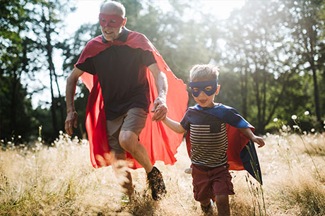 Grandfather running with his grandson dressed up as super heros